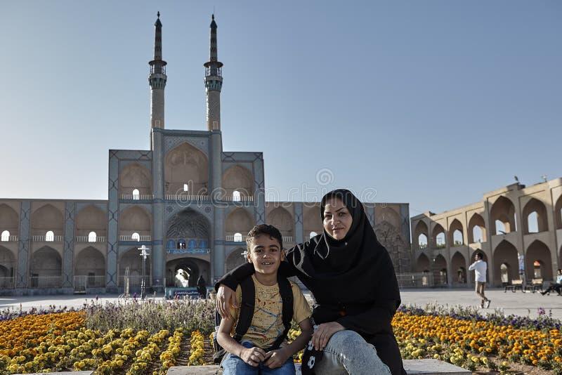 La mujer musulmán y su hijo descansan cerca de una mezquita, Irán fotos de archivo