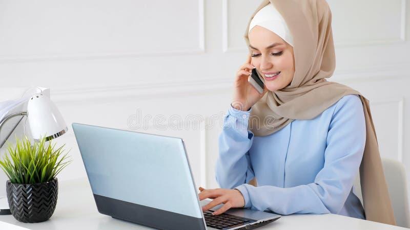 La mujer musulm?n en hijab est? hablando el tel?fono m?vil y est? mecanografiando en el ordenador port?til en el trabajo de ofici fotos de archivo