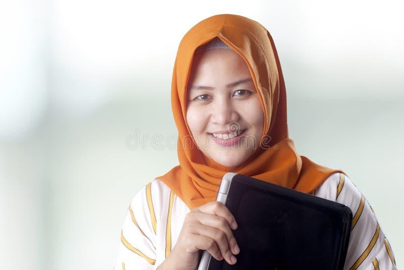 La mujer musulm?n sostiene el ordenador port?til fotos de archivo