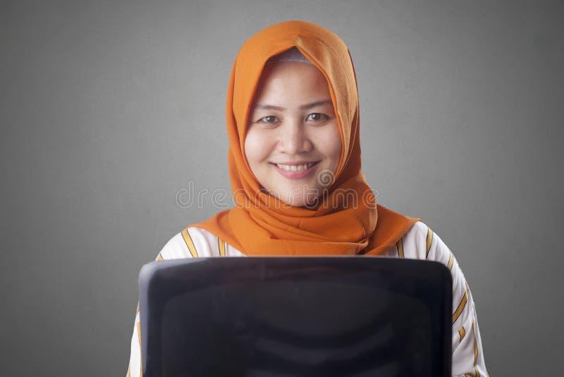 La mujer musulm?n sostiene el ordenador port?til imagen de archivo libre de regalías