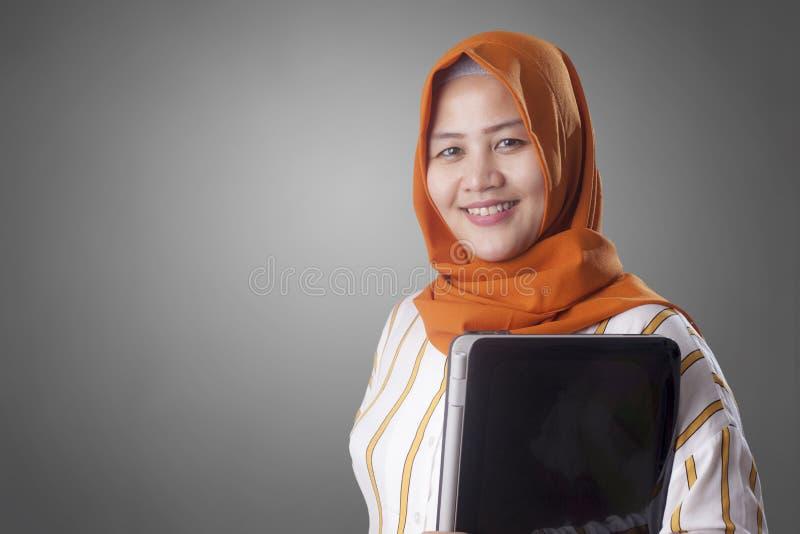 La mujer musulm?n sostiene el ordenador port?til fotos de archivo libres de regalías