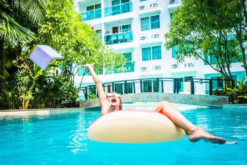 La mujer nada en la piscina en la piscina y lanza el ordenador portátil en el agua La muchacha está descansando sobre el mar en fotografía de archivo libre de regalías