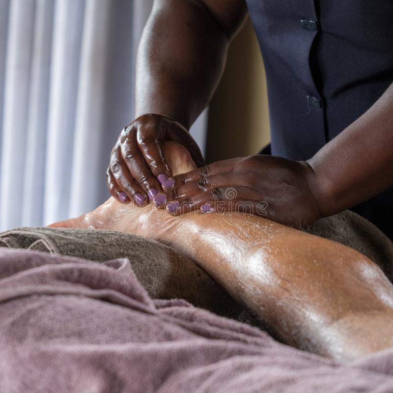 La mujer negra da un masaje del pie a un hombre caucásico mayor fotos de archivo libres de regalías