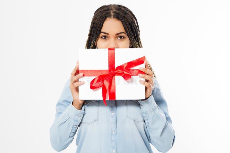 La mujer negra hermosa oculta su cara detrás de una caja de regalo en un fondo blanco foto de archivo libre de regalías