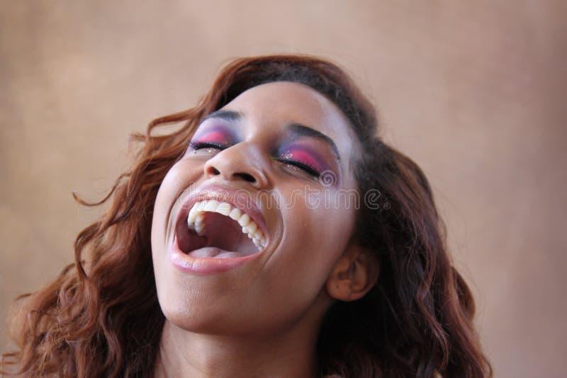 La mujer negra hispánica joven levanta a su cabeza para arriba que ríe fotos de archivo libres de regalías