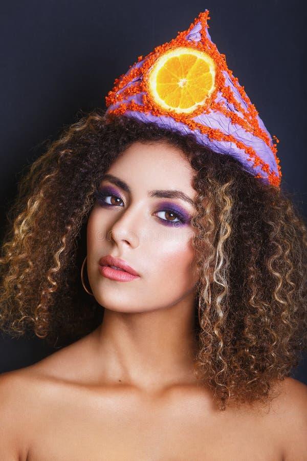 La mujer negra joven con el peinado afro y compone Mujer étnica con la diadema de la flor y de la fruta imagenes de archivo