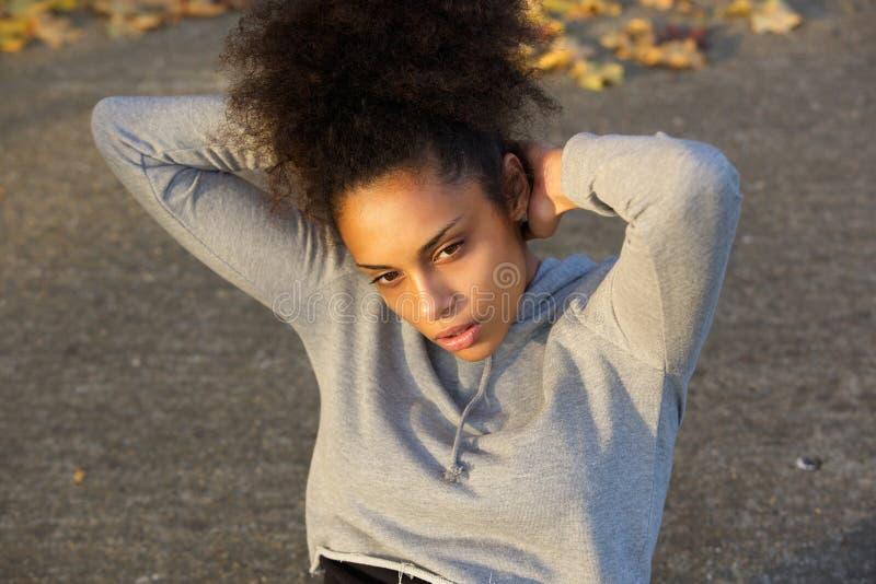 La mujer negra joven que ejercita cerca se sienta sube imagen de archivo