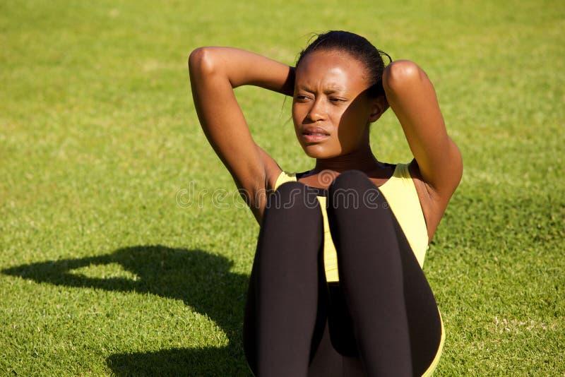 La mujer negra joven sana que el hacer se sienta sube al aire libre en hierba foto de archivo libre de regalías