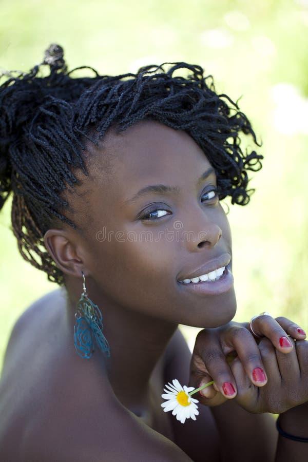 La mujer negra joven tejido el retrato al aire libre de la flor imagen de archivo