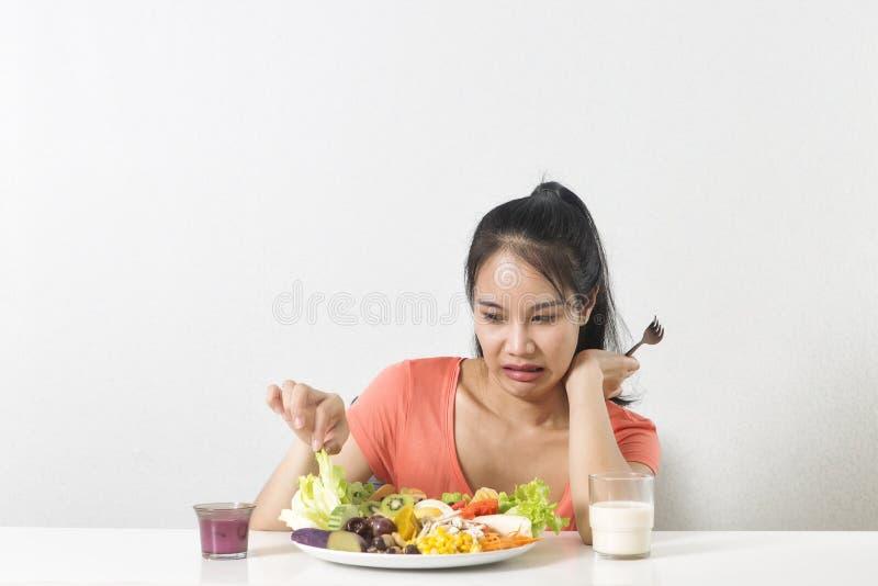 La mujer no le gusta la verdura La mujer infeliz no le gusta la comida sana foto de archivo libre de regalías