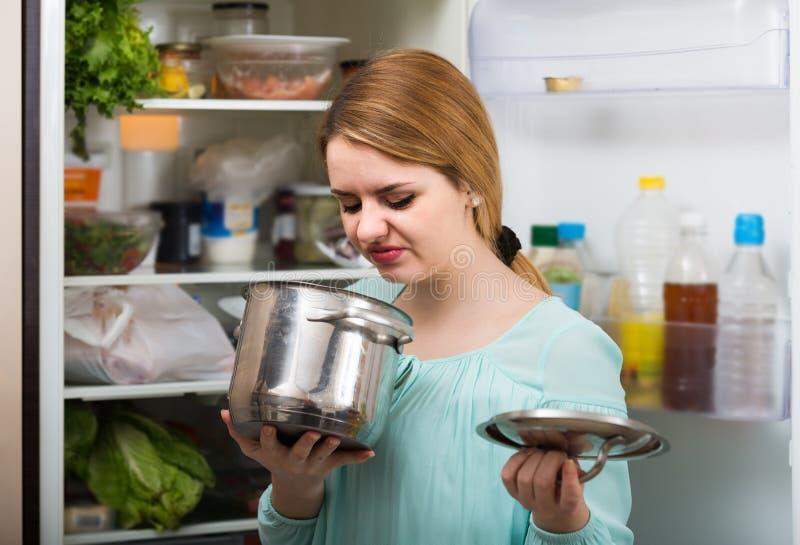 La mujer notó el olor asqueroso de la comida de la cazuela imagenes de archivo