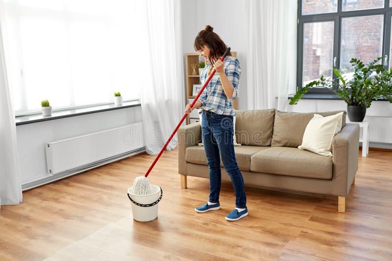 La mujer o el ama de casa con la limpieza de la fregona suela en casa imagenes de archivo