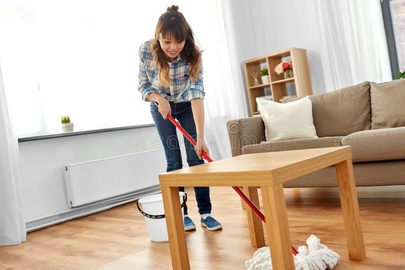 La mujer o el ama de casa con la limpieza de la fregona suela en casa imágenes de archivo libres de regalías