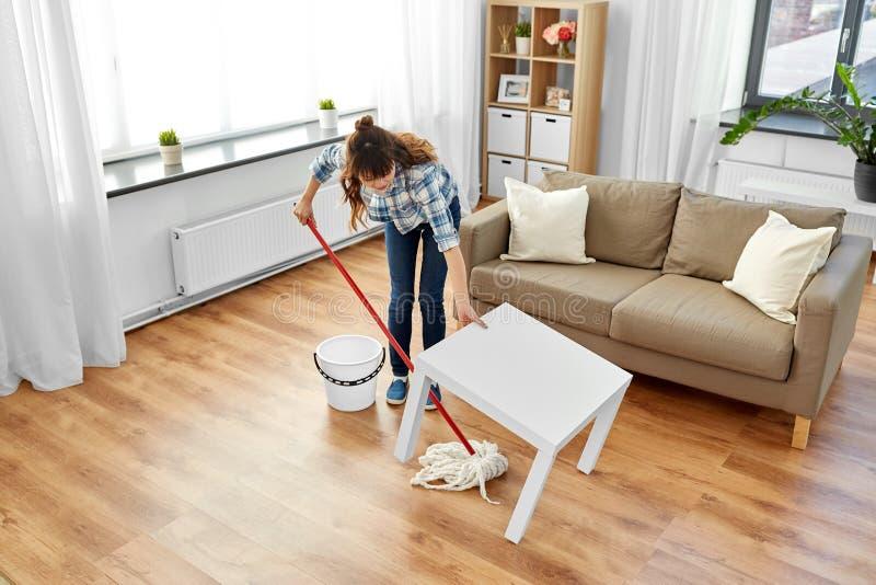 La mujer o el ama de casa con la limpieza de la fregona suela en casa fotografía de archivo libre de regalías