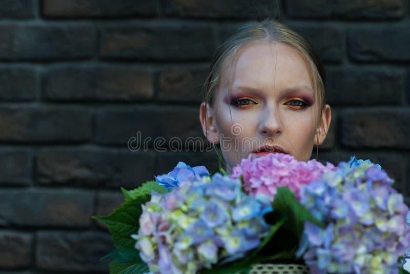 La mujer o la muchacha con hortensia florece en la pared de ladrillo fotos de archivo