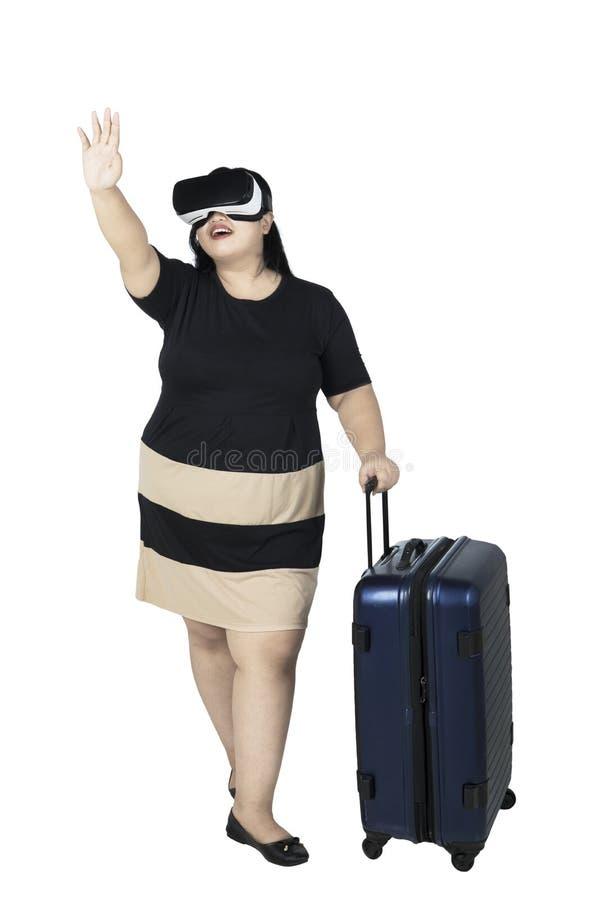 La mujer obesa está utilizando las auriculares de la realidad virtual foto de archivo