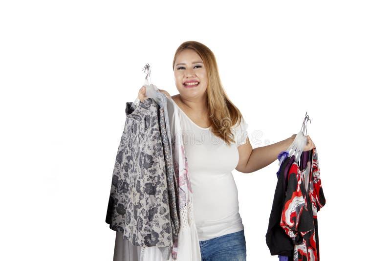 La mujer obesa sostiene mucha ropa fotografía de archivo