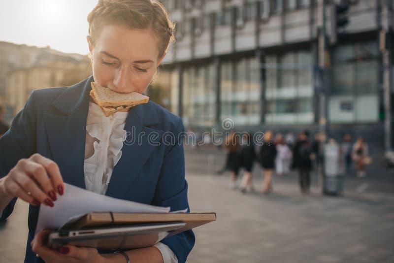 La mujer ocupada tiene prisa, ella no tiene tiempo, ella va a comer el bocado en camino Trabajador que come, café de consumición imagenes de archivo