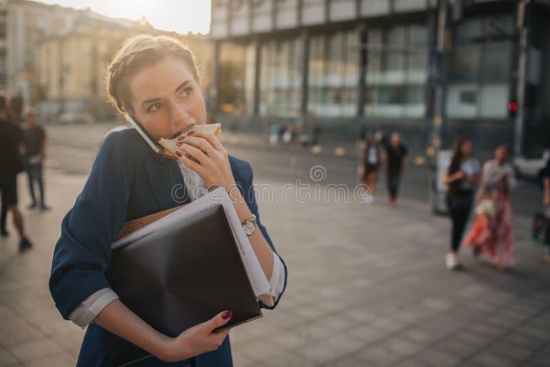 La mujer ocupada tiene prisa, ella no tiene tiempo, ella va a comer el bocado en camino Trabajador que come, café de consumición imagen de archivo