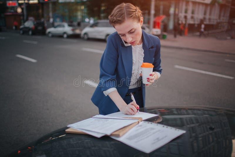 La mujer ocupada tiene prisa, ella no tiene tiempo, ella va a hablar en el teléfono en camino El hacer de la empresaria imagen de archivo libre de regalías
