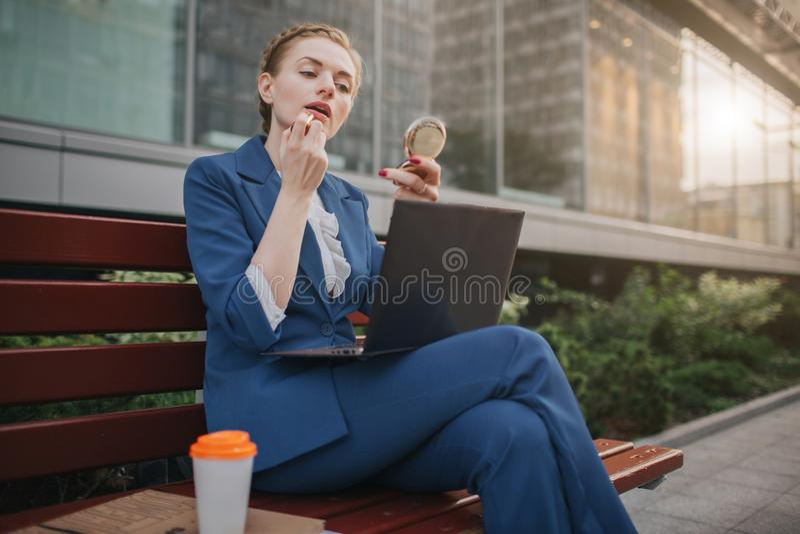 La mujer ocupada tiene prisa, ella no tiene tiempo, ella va a hacer compone y a trabajar en el ordenador portátil Aplicación del  foto de archivo