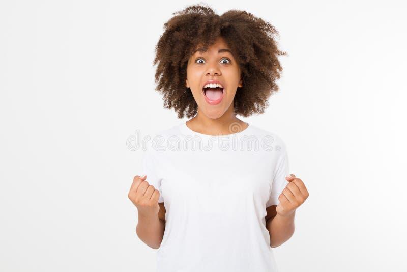 La mujer oscura joven feliz de la piel aislada en el fondo blanco en camiseta viste Copie el espacio Mofa para arriba Camiseta en fotografía de archivo libre de regalías