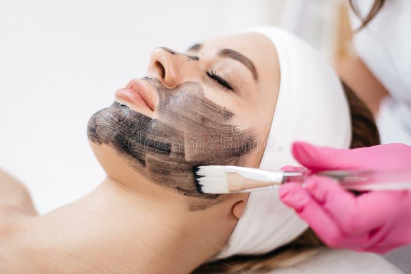 La mujer pacífica atractiva joven está recibiendo la máscara negra en su cara Las manos del cosmetólogo que lo aplican con imagen de archivo
