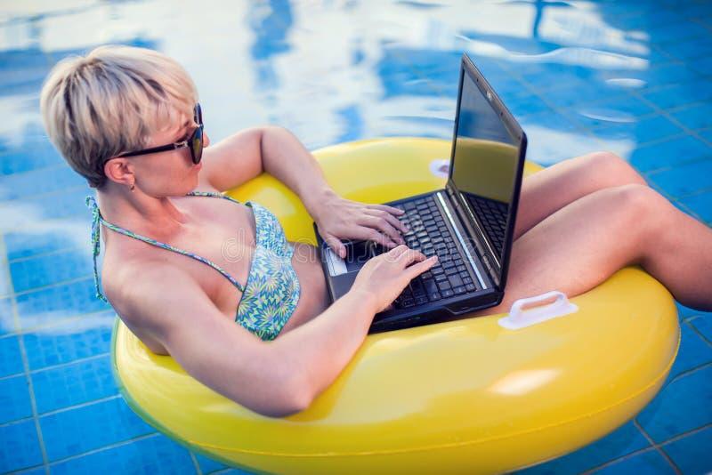 La mujer pasa tiempo, lo tiene relajarse y trabajar con el ordenador portátil en la piscina Concepto de la gente, del verano y de fotos de archivo libres de regalías