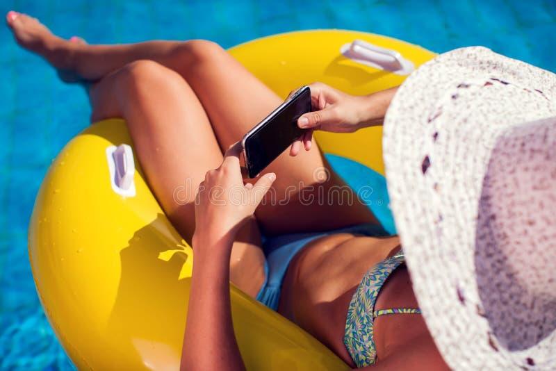 La mujer pasa tiempo y lo tiene relajarse en la piscina con el teléfono Concepto de la gente, del verano y del día de fiesta imagenes de archivo