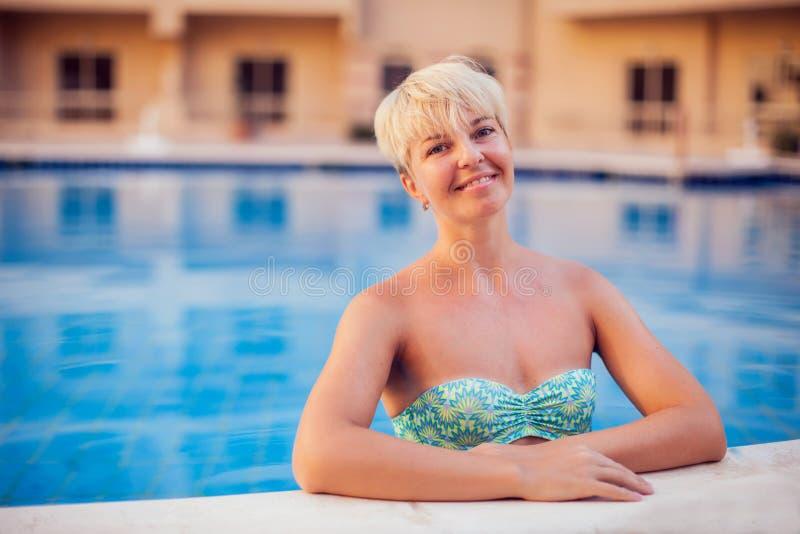 La mujer pasa tiempo y lo tiene relajarse en la piscina Concepto de la gente, del viaje, del verano y del día de fiesta fotografía de archivo libre de regalías
