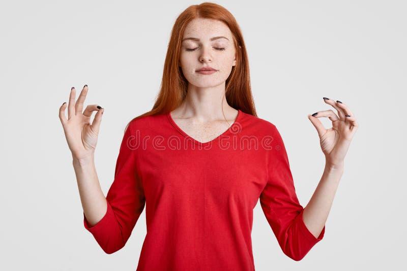 La mujer pecosa pelirroja tranquila medita en estudio, hace gesto aceptable con ambas manos, vestidas en ropa casual roja disfrut fotografía de archivo