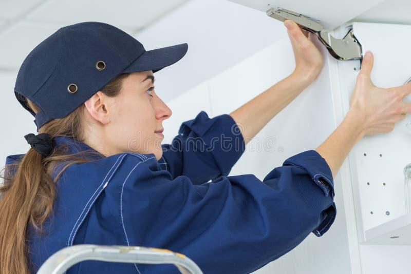 La mujer pega el azulejo del techo fotografía de archivo libre de regalías