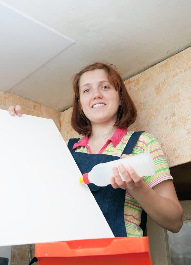 La mujer pega el azulejo del techo fotografía de archivo