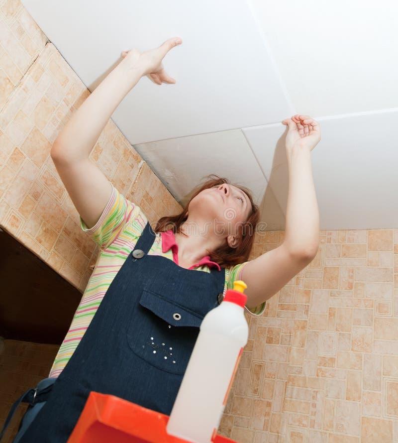 La mujer pega el azulejo del techo foto de archivo