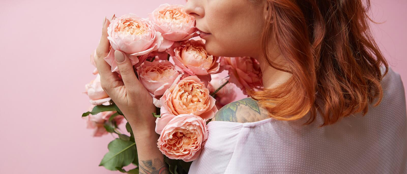 La mujer pelirroja con el tatuaje en sus hombros sostiene rosas coralinas frescas delicadas en un fondo coralino vivo Un regalo p imágenes de archivo libres de regalías
