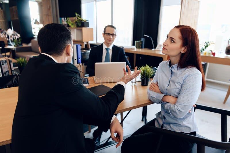 La mujer pelirroja, descontenta, con sus manos abrochadas juntas, escucha el hombre en traje en oficina del ` s del abogado imagenes de archivo