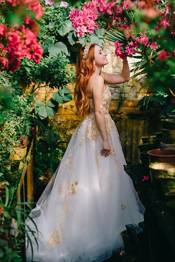 La mujer pelirroja hermosa inhala el olor de flores florecientes imágenes de archivo libres de regalías