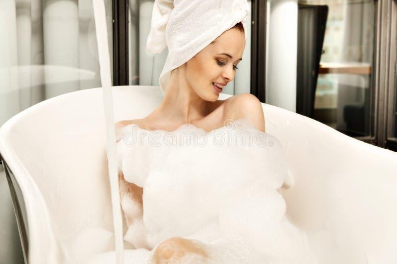 La mujer pelirroja hermosa joven toma el baño de burbujas fotografía de archivo