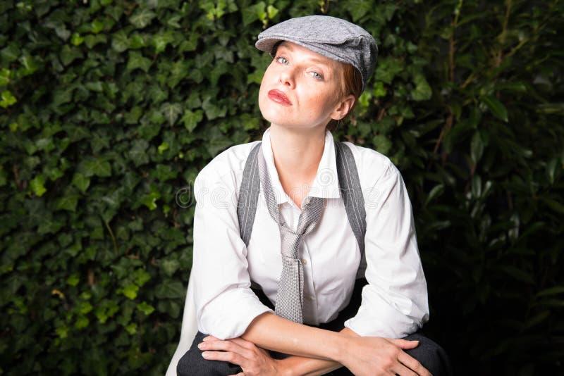 La mujer pelirroja joven como hombre vestido en el jardín hace en m fotografía de archivo