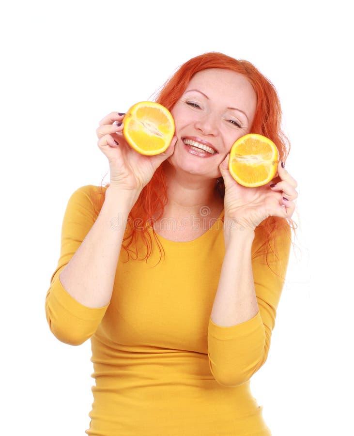 La mujer pelirroja joven que juega con las naranjas frescas da fruto fotografía de archivo libre de regalías