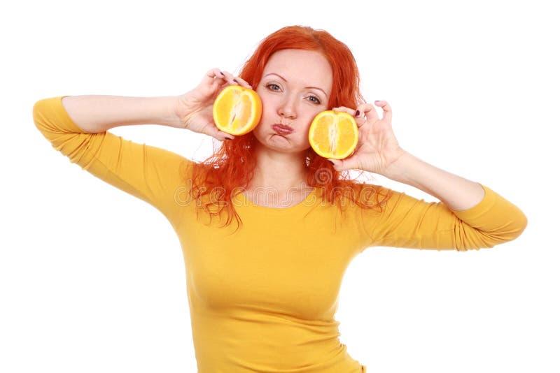 La mujer pelirroja joven que juega con las naranjas frescas da fruto fotografía de archivo