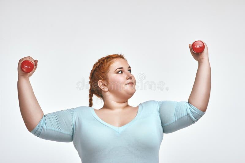 La mujer pelirroja, rechoncha divertida es sonriente y que lleva a cabo pesas de gimnasia foto de archivo