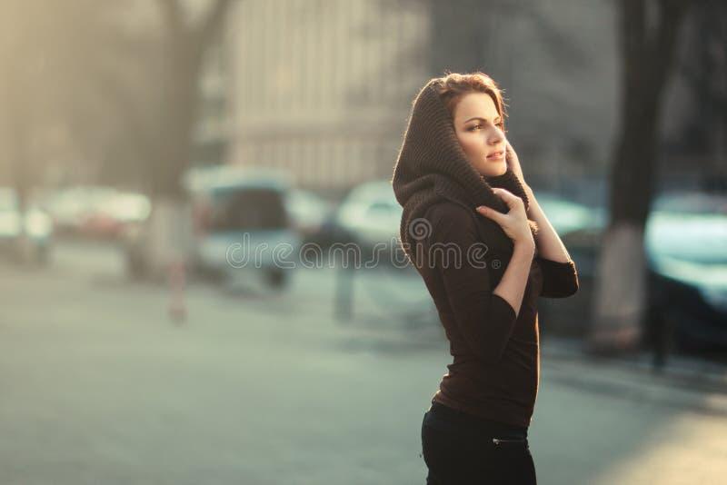 La mujer pensativa en la ciudad de la puesta del sol imagen de archivo