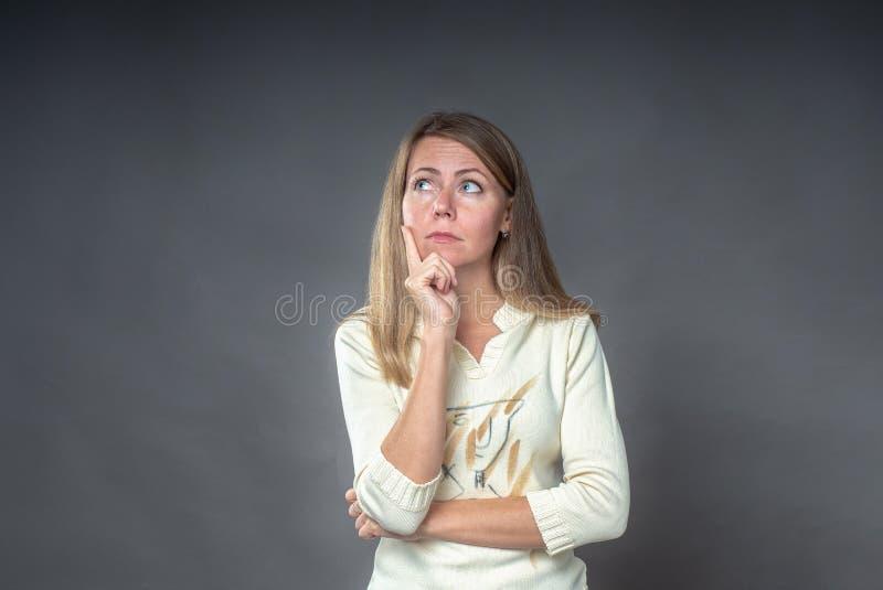 La mujer pensativa mira a un lado con la expresión pensativa, planes algo con muchas preguntas en su cabeza Hembra desconcertada foto de archivo libre de regalías