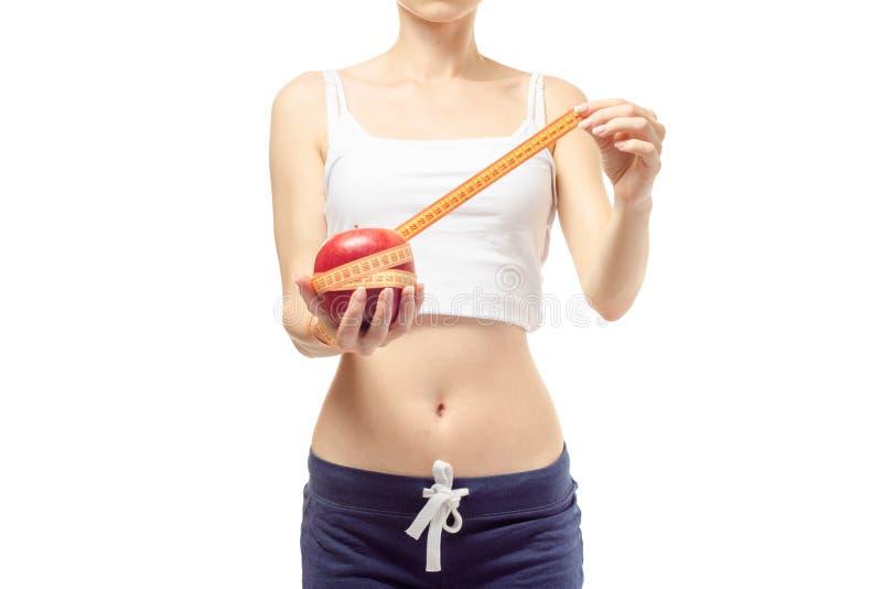 La mujer pierde la manzana del centímetro de la delgadez del peso foto de archivo