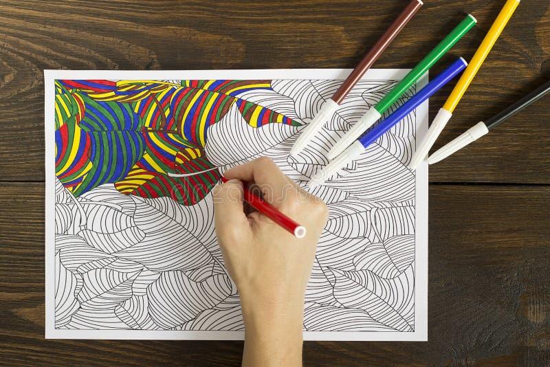 La mujer pinta el libro de colorear para los adultos fotografía de archivo