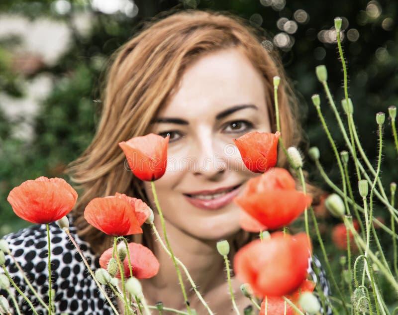 La mujer positiva caucásica joven con la amapola de maíz florece, la belleza a imagenes de archivo