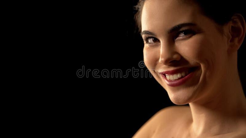La mujer positiva que sonríe en la cámara, en fondo negro, compone el estudio fotografía de archivo