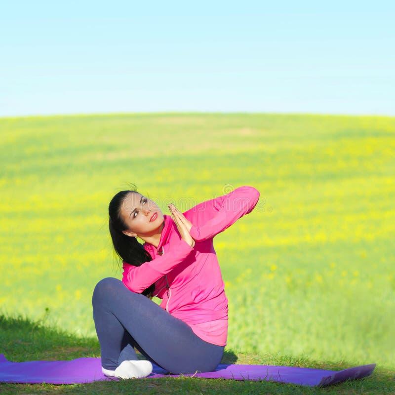 La mujer practica yoga fotografía de archivo