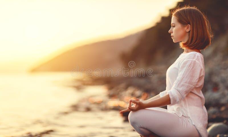 La mujer practica yoga y medita en la posición de loto respecto a la puesta del sol b fotografía de archivo